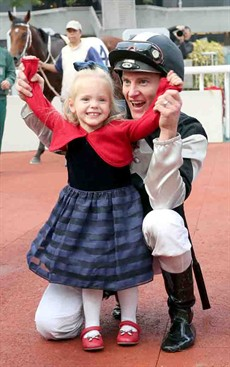Zac Purton celebrates his treble, culminating in his win aboard Exultant, with daughter Roxy in the Sha Tin winners' circle.